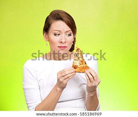 Closeup portrait conflicted, young woman holding, desiring fatty pizza, not sure if she should eat because extra calories, isolated green background. Negative emotion facial expression feelings - stock photo