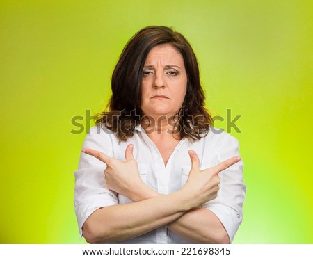Closeup portrait confused middle aged woman pointing in two different directions, not sure which way to go in life isolated green background. Negative emotion facial expression feeling body language - stock photo