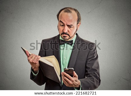 Closeup portrait confused, skeptical business man, executive reading news on smart phone, holding book isolated grey wall background. Human face expression, emotion, body language, corporate lifestyle - stock photo