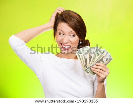 Closeup portrait, confused stressed woman holding cash dollars in hand, scratching head wondering how to spend. More money, more problems concept. Negative human emotions, facial expressions, feelings - stock photo