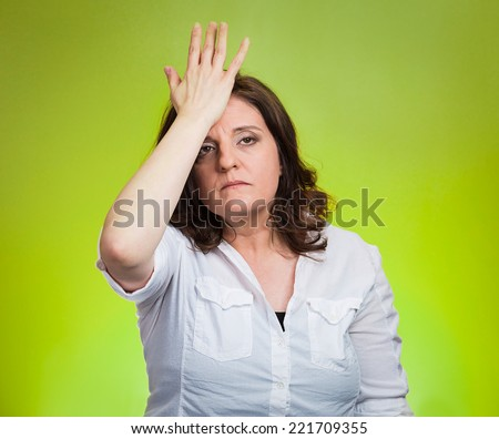 Closeup portrait confused young woman placing hand on head, palm on face gesture in duh moment isolated green background. Negative emotion facial expression feeling body language, life perception - stock photo