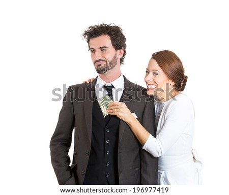 Closeup portrait couple, excited woman, girlfriend pulling money out of man pocket, he looks skeptical, surprised, isolated white background. Shopping lover, reckless spending. Human face expressions - stock photo