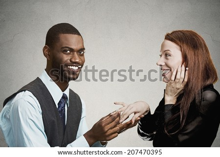 Closeup portrait couple, handsome happy man proposing to excited smiling young woman isolated grey black background. Holidays, love, relationship dating concept. Human face expression emotion feelings - stock photo
