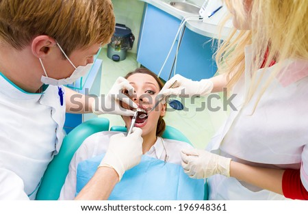 Closeup portrait dentist, his assistant carrying out thorough examination dental procedure, tooth extraction on young female patient, lying in chair, wide open mouth isolated clinic office background - stock photo