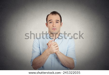 Closeup portrait desperate young man showing clasped hands, pretty please with sugar on top isolated grey wall background. Human emotion facial expression feelings, signs symbols body language - stock photo