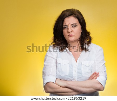 Closeup portrait displeased pissed off angry grumpy pessimistic woman with bad attitude, arms crossed looking at you, isolated yellow background. Negative human emotion facial expression feeling - stock photo