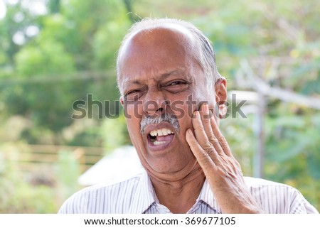 Closeup portrait elderly business man with tooth ache crown problem cavity grimacing from pain touching outside mouth with hand isolated outside background. Negative human emotion facial expression  - stock photo