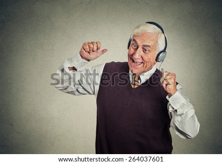 Closeup portrait elderly man, senior retired guy with headphones listening to the radio, enjoying music and his life isolated on gray wall background. Positive human emotions, face expression   - stock photo