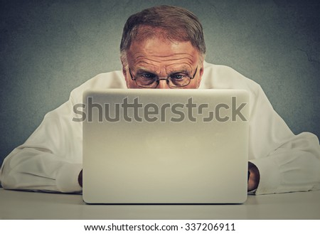 Closeup portrait elderly man sitting at table working on laptop computer isolated on gray office wall background