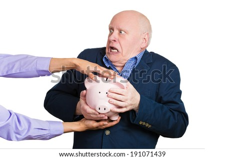Closeup portrait elderly, shocked senior business man, grandfather, holding piggy bank, looking scared trying to protect his savings from being stolen isolated white background. Financial fraud, crime - stock photo
