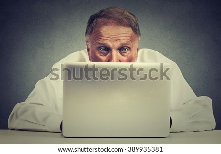 Closeup portrait elderly surprised man sitting at table working on laptop computer looking carefully at screen isolated on gray office wall background - stock photo