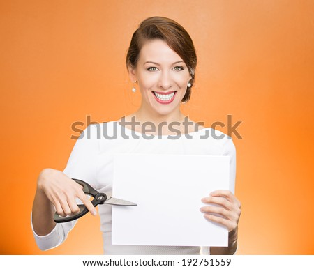 Closeup portrait, excited, happy, energetic enthusiastic young business woman, funny female, worker, dedicated employee cutting blank white paper, copy space with scissors isolated orange background. - stock photo