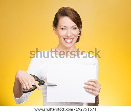 Closeup portrait, excited, happy, energetic enthusiastic young business woman, funny female, worker, dedicated employee cutting blank white paper, copy space with scissors isolated yellow background. - stock photo