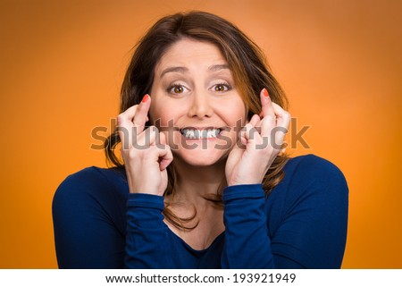 Closeup portrait excited, smiling, hopeful beautiful woman, mother crossing her fingers hoping, asking for best isolated orange background. Human face expressions, emotions, feeling, attitude reaction - stock photo