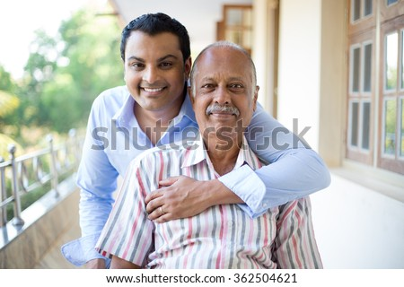 Closeup portrait, family, young man in blue shirt holding older man in striped shirt from behind, happy isolated on outdoors outside balcony background - stock photo