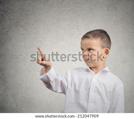 Closeup portrait funny looking grumpy boy with disgust on his face presenting, pointing at black copy space to his left, isolated grey wall background. Negative human face expression, emotions feeling - stock photo