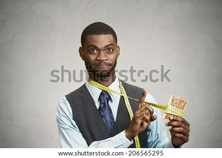 Closeup portrait funny young, confused man holding fatty, sweet cookie with measuring tape around, trying to withstand resist, avoid temptation to eat it isolated black background. Face expressions - stock photo