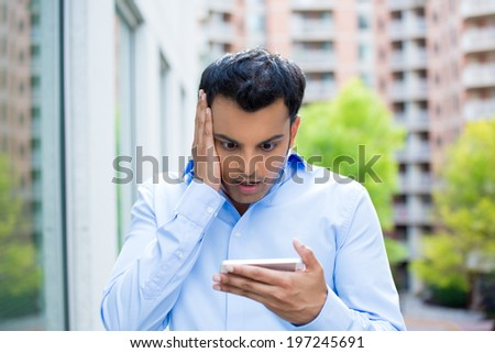 Closeup portrait, funny young man, shocked surprised, wide open mouth, by what he sees on his cell phone, isolated outdoors building background. Negative human emotions, facial expression feeling - stock photo