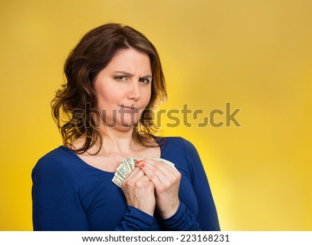 Closeup portrait greedy middle aged woman corporate business employee, worker, student holding dollar banknotes tightly isolated yellow background. Negative human emotion facial expression feeling - stock photo