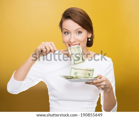 Closeup portrait greedy, young ceo, corporate executive, manager, business woman eating green cash, money dollars from plate, isolated yellow background. Emotion, facial expression. Financial avarice.