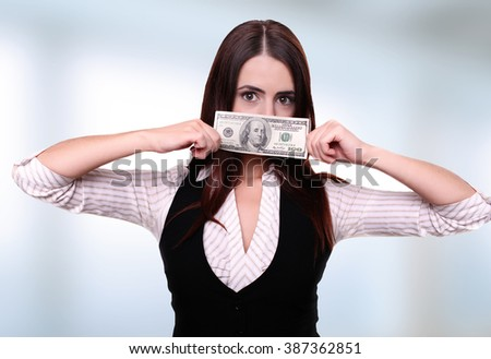 Closeup portrait greedy young woman corporate business employee, worker, student holding dollar banknotes tightly, isolated white background. Negative human emotion facial expression - stock photo