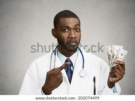 Closeup portrait grumpy greedy miserly health care professional, male doctor holding, pointing at his money dollars in hand isolated black background. Negative human emotion facial expression attitude - stock photo