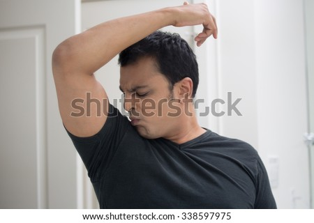 Closeup portrait, grumpy sweaty young man in black t-shirt, sniffing himself, very foul situation, isolated mirror reflection. Negative human emotions, facial expressions, feelings - stock photo