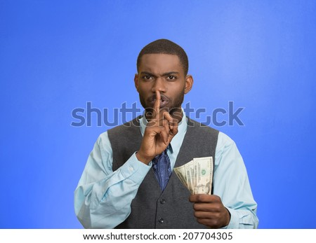 Closeup portrait handsome corrupt guy businessman holding dollar bill in hand showing shhh sign finger to lips isolated blue background. Bribery concept politics, business diplomacy. Face expression - stock photo