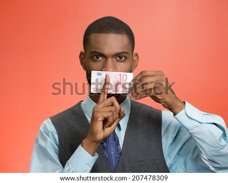 Closeup portrait handsome corrupt guy, businessman holding euro bill currency to mouth, showing shhh sign, isolated red background. Bribery concept in politics, business, diplomacy. Face expressions - stock photo