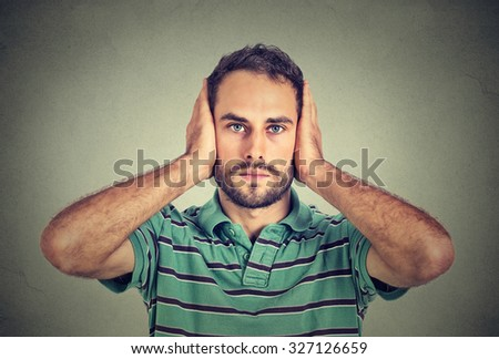Closeup portrait handsome, peaceful, tranquil, looking relaxed, young man covering his ears, observing isolated on gray wall background. Hear no evil concept. Human emotion facial expression - stock photo
