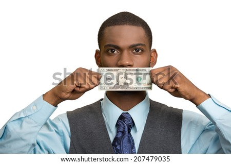Closeup portrait handsome young corrupt corporate man in blue shirt holding twenty dollar bill to mouth, isolated white background. Bribery concept in politics, business, diplomacy. Life perception - stock photo