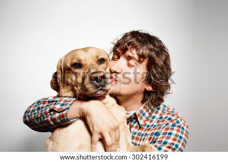 Closeup portrait handsome young hipster man, kissing his good friend dog isolated black grey background. Positive human emotions, facial expression, feelings. - stock photo
