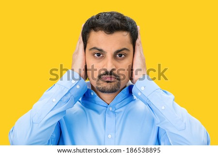 Closeup portrait, handsome young man covering, closing his ears with hands, eyes observing, closed mouth, isolated yellow background. Hear no evil concept. Human emotion, facial expression - stock photo