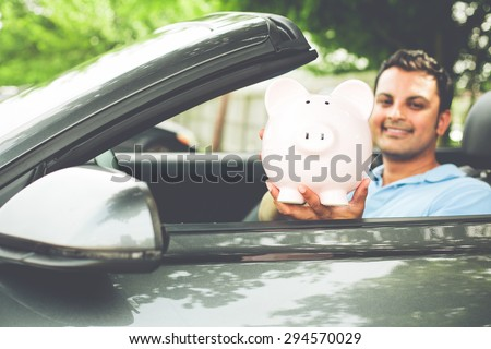 Closeup portrait, handsome young man in blue polo shirt showing pink piggy bank inside new sports car, isolated outdoors background.  Happy to have good low apr interest rates, finance rebate deals  - stock photo