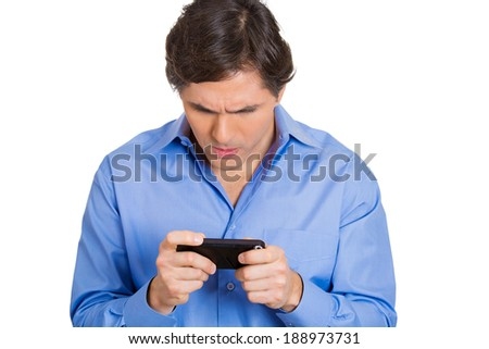 Closeup portrait. handsome young man, unhappy, mad, frustrated, by what he sees on his cell phone, isolated white background. Negative human emotions, facial expressions, feeling - stock photo