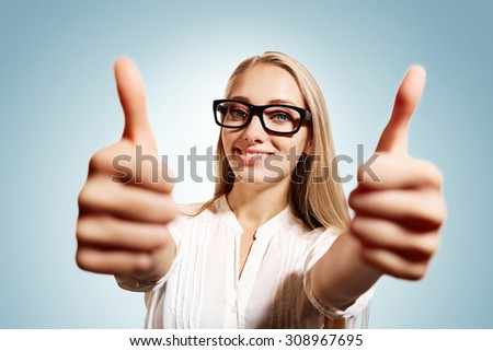 Closeup portrait handsome young smiling blonde business woman, corporate employee giving thumbs up sign at camera at blue background. Positive human emotions, facial expression, feelings. - stock photo