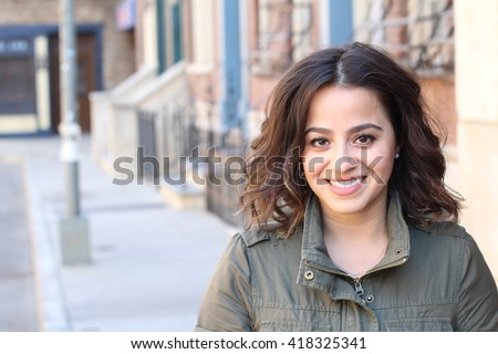 Closeup portrait, happy beautiful, smiling young woman in green jacket, posing on outdoors sidewalk, isolated on background with buildings, city urban life - stock photo