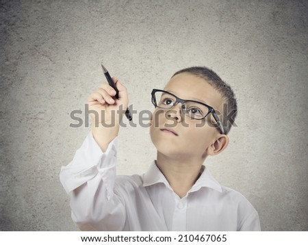 Closeup portrait happy boy, little man, student with glasses writing with pen on blackboard, isolated grey wall background with copy space.  Education, knowledge concept. Positive face expressions - stock photo