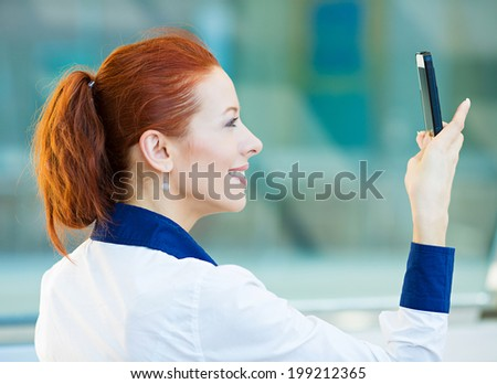 Closeup portrait, happy, cheerful, excited girl, using cell phone, taking picture isolated background corporate office. Facial expression, reaction. Business woman sending text message from mobile. - stock photo