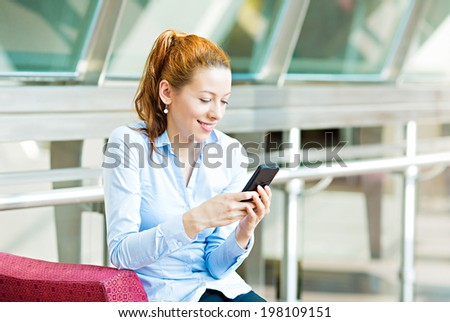 Closeup portrait, happy, cheerful, girl, excited by what she sees on cell phone, isolated background corporate office. Facial expression, reaction. Business woman sending text message from her mobile - stock photo