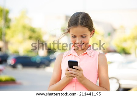 Closeup portrait happy, cheerful, girl, excited by what she sees on cell phone isolated outdoor street background. Positive Facial expressions, reaction. Teenager sending text message from her mobile - stock photo