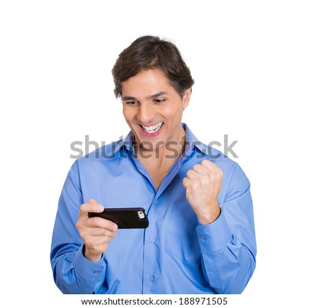 Closeup portrait, happy, cheerful, young adult man, excited by what he sees on his cell phone, isolated white background. Positive human emotions, facial expression, feelings, reaction