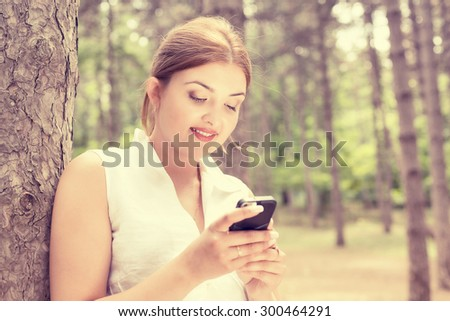 Closeup portrait, happy, cheerful, young woman excited by what she sees on cell phone sitting outdoors in park. Facial expression, reaction. Smiling girl sending text message from her mobile - stock photo