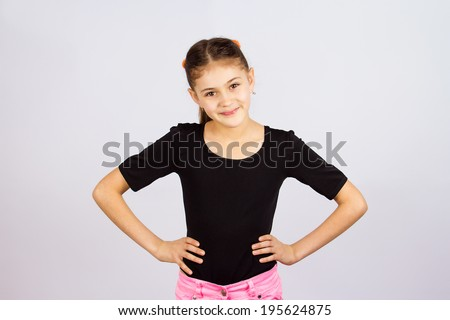 Closeup portrait happy confident successful little girl in black t-shirt ready for challenge asking ok whats next arms on waist gesture, isolated grey background. Positive emotion expression attitude - stock photo