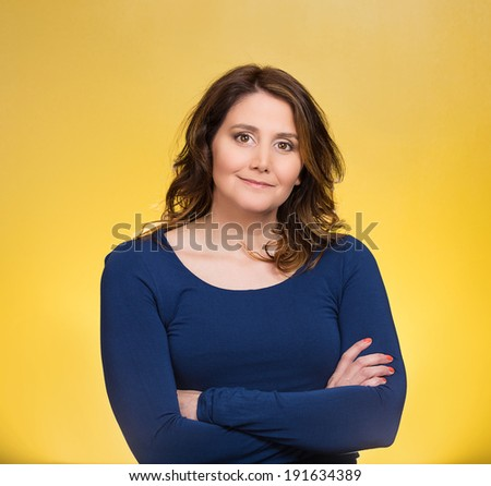 Closeup portrait, happy, confident, successful, pretty young woman in blue shirt with arms crossed folded, isolated yellow background. Positive human emotions, facial expressions, feelings, attitude - stock photo