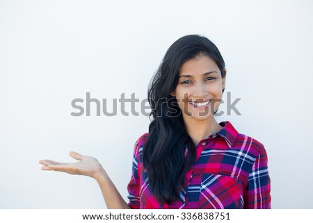 Closeup portrait happy confident young smiling woman gesturing, presenting space at left with palm up isolated white wall background. Positive human emotion signs symbol, facial expression feelings - stock photo
