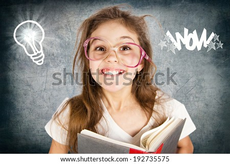 Closeup portrait happy, excited, smiling, funny looking little girl with glasses, holding book, discovered something new, isolated blackboard with light bulb. Human facial expression, emotion, feeling - stock photo
