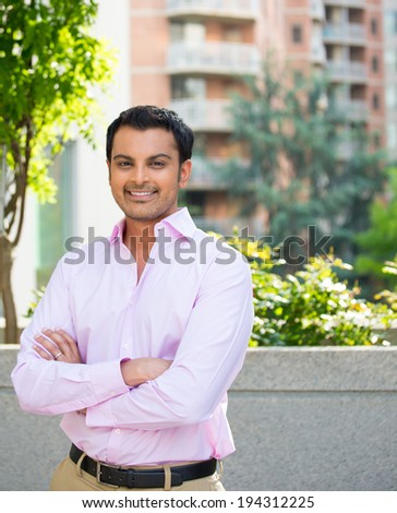 Closeup portrait, happy handsome businessman in pink shirt, arms folded, crossed, relaxing outside of his office during sunny day, isolated city urban balcony background. Corporate success - stock photo