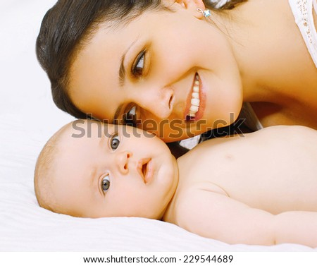 Closeup portrait happy mom and baby in bed - stock photo