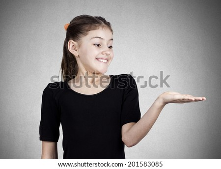 Closeup portrait happy pretty confident young smiling girl gesturing to space at right with palm up isolated grey, black background. Positive human emotions, signs symbol, facial expression feelings - stock photo